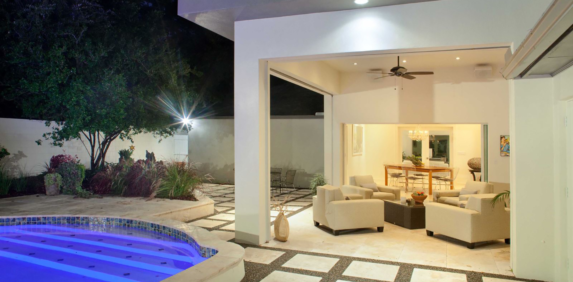 A photo of a residential backyard with pool, patio and lounge chairs